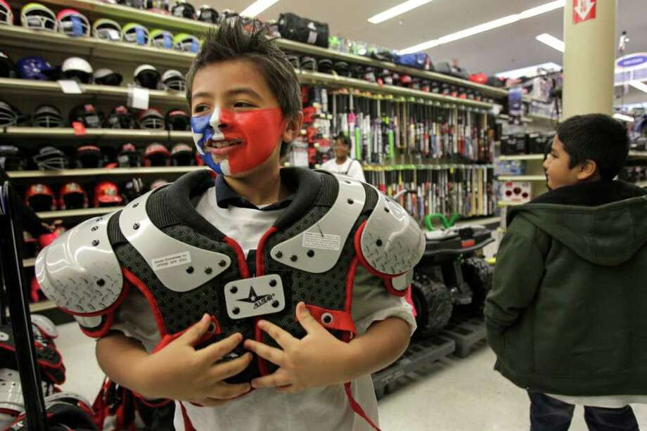 Victor Blancas, 8, tries on football shoulder pads as his shops during the annual Shop With A Texan event at Academy Sports + Outdoors, 2404 SW Freeway, Tuesday, Dec. 13, 2011, in Houston. The Texans' rookie class, headlined by T.J. Yates, J.J. Watt and Brooks Reed, took 30 boys and girls on a shopping spree. Photo: Melissa Phillip, Houston Chronicle / © 2011 Houston Chronicle