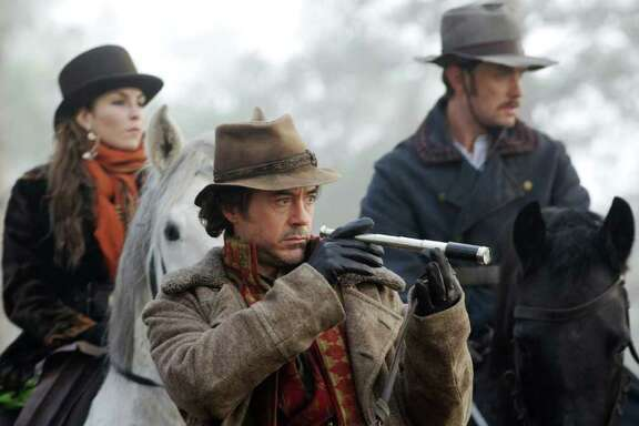"(L-r) NOOMI RAPACE as Madam Simza Heron, ROBERT DOWNEY JR. as Sherlock Holmes and JUDE LAW as Dr. James Watson in ""SHERLOCK HOLMES: A GAME OF SHADOWS"""