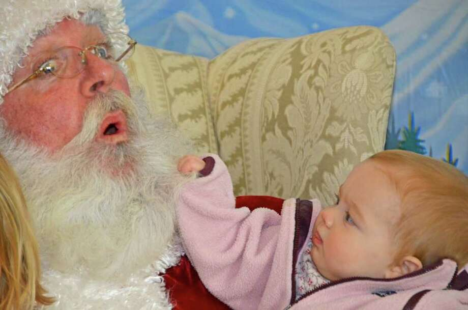 OH HO HO!  Little Kate Sorenson surprises Santa with a jolly tug during the New Canaan Nature Center Winter Wonderland festivities last Saturday, December 10, 2011. Photo: Jeanna Petersen Shepard