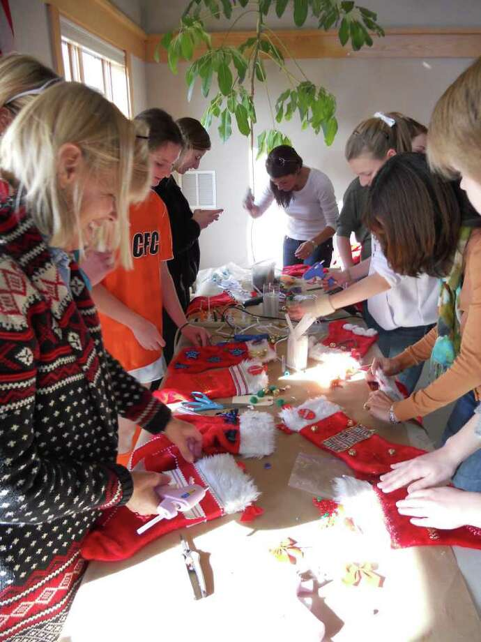 Women and girls from the Redding Chapter of the National Charity League piece together Christmas stockings, which they planned to fill with gifts for the homeless in Fairfield. The effort was part of Operation Hope's Hope for the Holidays gift drive. Photo: Contributed Photo / Fairfield Citizen contributed