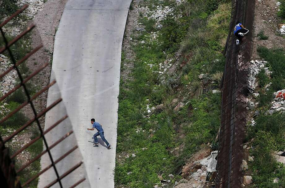 FILE - In this July 28, 2011 file photo, two men illegally cross the border fence separating Nogales, Ariz., and Nogales, Sonora, Mexico. The Supreme Court agreed Monday, Dec. 12, 2011 to rule on Arizona's controversial law targeting illegal immigrants. The justices said they will review a federal appeals court ruling that blocked several tough provisions in the Arizona law. One of those requires that police, while enforcing other laws, question a person's immigration status if officers suspect he is in the country illegally. (AP Photo/Jae C. Hong, File) Photo: Jae C. Hong, AP