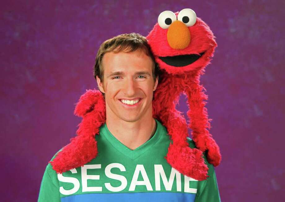 In this undated handout photo provided by Sesame Street, New Orleans Saints quarterback Drew Brees poses with Sesame Street puppet character 'Elmo' in New York,  Brees is making a special appearance on Thursday, Dec. 15, 2011 episode of the educational children's TV show. He visited the set a few months ago to record the segment, which co-stars the street's furry red resident, Elmo. (AP Photo/ Sesame Street, Jesse Grant) Photo: Jesse Grant