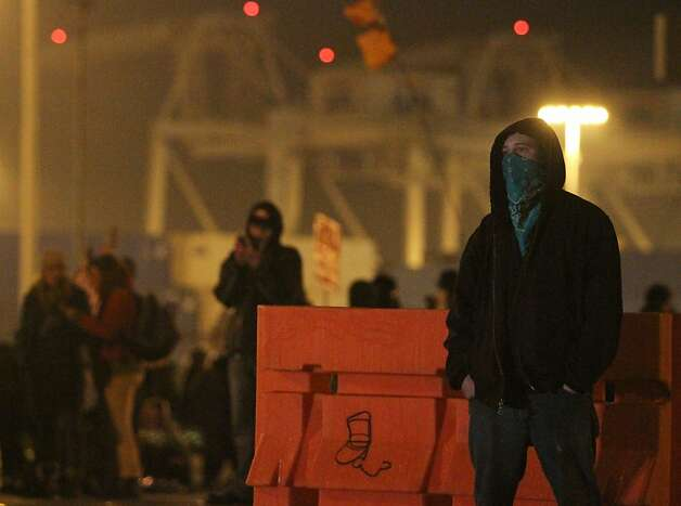 A protestor stands in front of a barricade at the Port of Oakland after Occupy Oakland forced a shut down of the shipping facility on Tuesday, Dec. 13, 2011 in Oakland, Calif. Photo: Mathew Sumner, Special To The Chronicle
