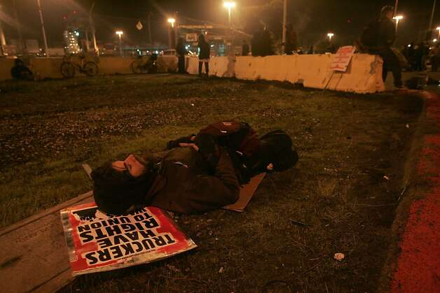 A protestor rests outside terminal 43 at the Port of Oakland after Occupy Oakland forced a shut down of the shipping facility on Monday, Dec. 12, 2011 in Oakland, Calif. Photo: Mathew Sumner, Special To The Chronicle