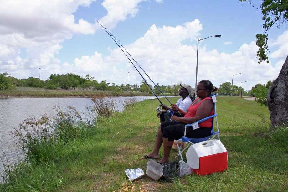 TOM BEHRENS: FOR THE CHRONICLE 'SHOPPING' FOR A MEAL: Fishing for rainbow trout is easy and relaxing. Here, a couple of anglers try their luck at Tom Bass Park in Houston. Photo: TOM BEHRENS
