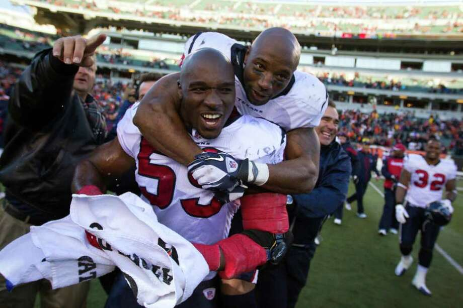Texans linebacker DeMeco Ryans (59) and safety Danieal Manning celebrate their win over the Bengals on Sunday. Photo: Smiley N. Pool, Houston Chronicle / © 2011  Houston Chronicle