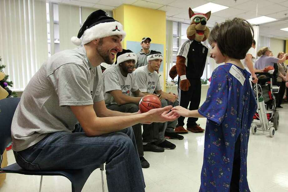Spurs' Manu Ginobili (left) reaches to shake hands with seven-year-old Gabriella Muñoz during a visit by San Antonio Spurs players at Christus Santa Rosa Children's Hospital on Tuesday, Dec. 13, 2011. Joining Ginobili were teammates James Anderson (second from left) and Danny Green. The visit by players marked the 15th year that patients from the hospital met with the team. About 50 patients and family members waited in line and received autographed miniature basketballs as souvenirs. Photo: Kin Man Hui / San Antonio Express-News