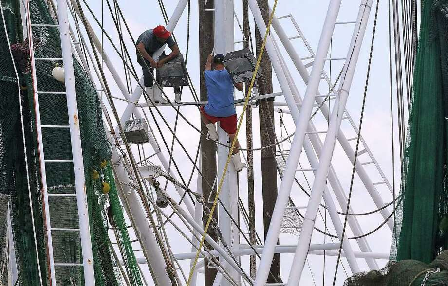 Two men repair a light on a shrimping boat in Sabine Pass on Wednesday. The Texas shrimping season opened at 12 am this morning. Guiseppe Barranco/The Enterprise Photo: Guiseppe Barranco / Beaumont