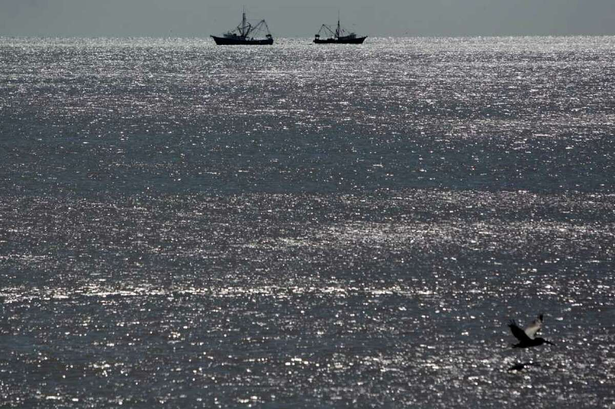 JOHNNY HANSON: HOUSTON CHRONICLE GULF SHRIMPERS: A pair of shrimp boats pass by each other while working in the Gulf of Mexico off the Galveston Seawall at 61st Street in October.