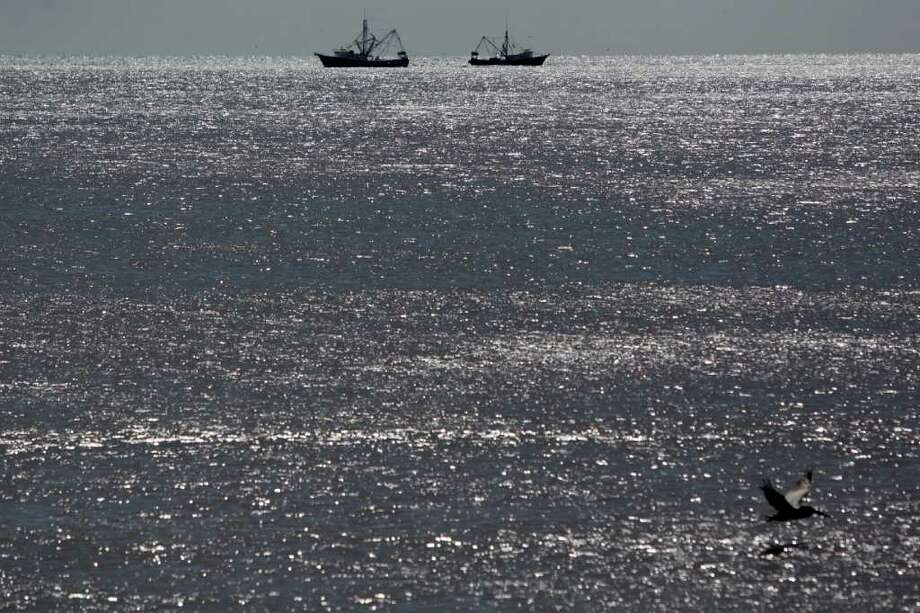 JOHNNY HANSON: HOUSTON CHRONICLE GULF SHRIMPERS: A pair of shrimp boats pass by each other while working in the Gulf of Mexico off the Galveston Seawall at 61st Street in October. Photo: Johnny Hanson / © 2011 Houston Chronicle