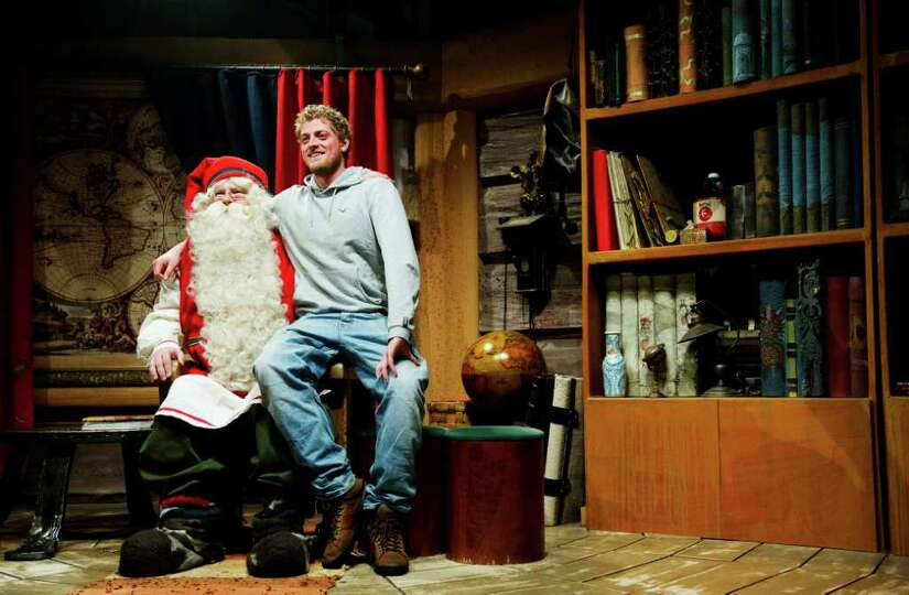 A tourist sits next to Santa Claus's as he visit him in his