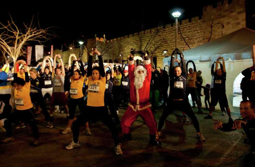 A Palestinian man dressed as Santa, warms up together with Israeli runners prior to a 10k night run,