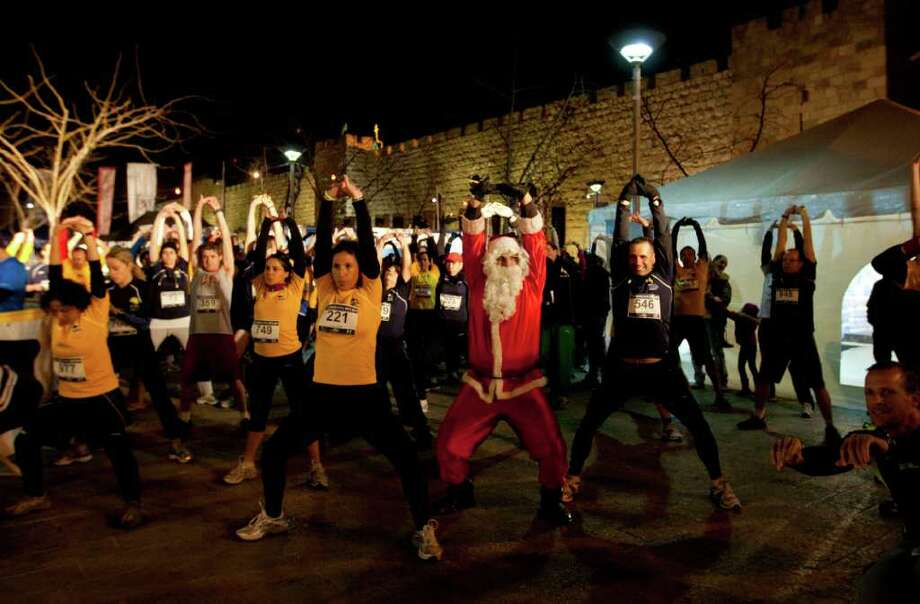 A Palestinian man dressed as Santa, warms up together with Israeli runners prior to a 10k night run, near the old city of Jerusalem,  Monday, Dec. 12, 2011. Photo: Sebastian Scheiner, Associated Press / AP