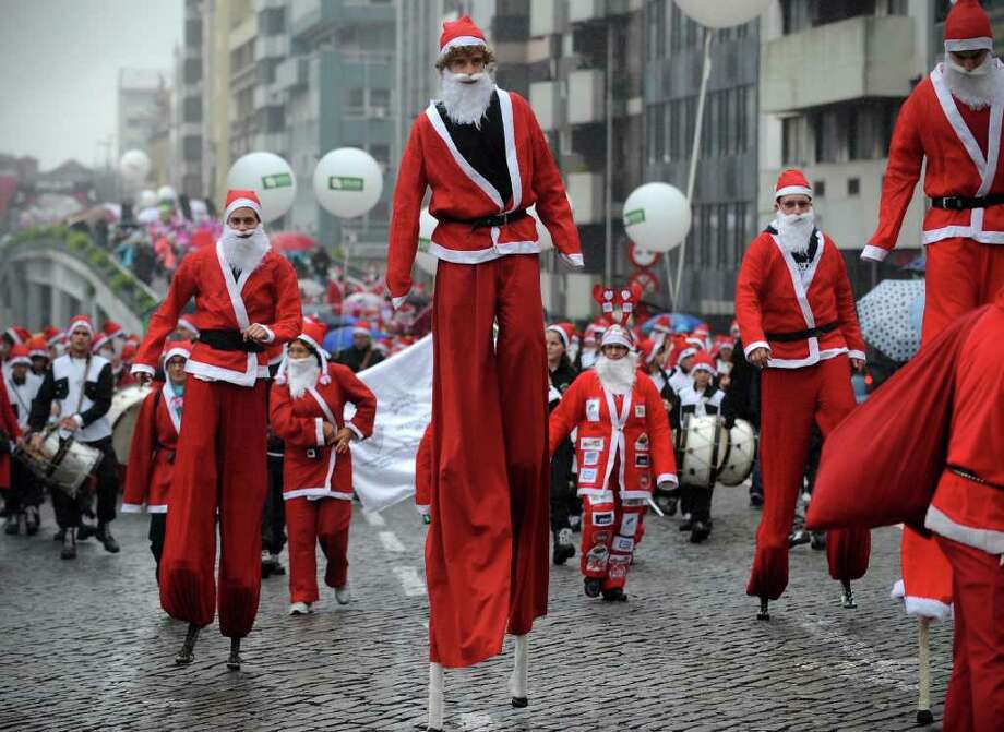 Performers dressed as Santa Claus participate in the annual Santa Claus parade, in Porto, Portugal, Sunday Dec. 11, 2011. Thousands staged a parade in an attempt to break the Guinness Book of records of most people dressed as Santa Claus. Photo: Paulo Duarte, Associated Press / AP