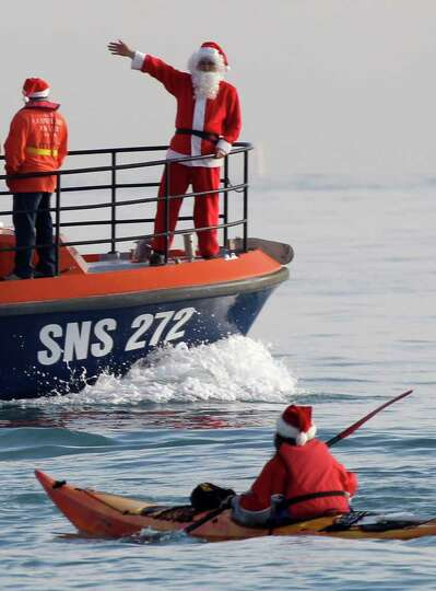 A man dressed as Santa Claus waves from the bow of a boat of the sea safety company on the Mediterra