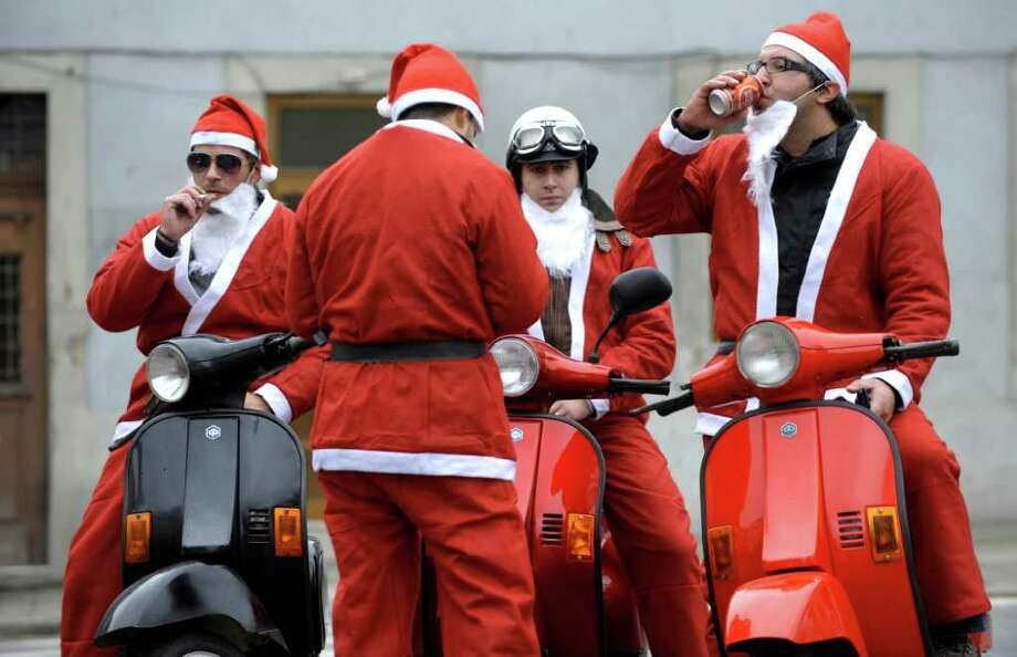 People dressed as Santa Claus take part in the annual Santa Claus parade in Porto, on December 11, 2011. Thousands staged a parade in an attempt to break the Guinness book of records of most people dressed as Santa Claus . Photo: MIGUEL RIOPA, Getty / AFP