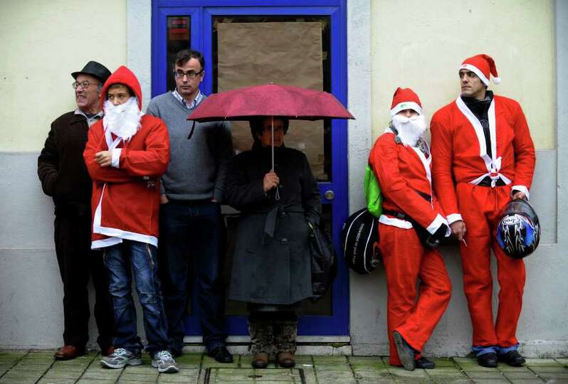 People dressed as Santa Claus wait to take part in the annual Santa Claus parade in Porto, on Decemb