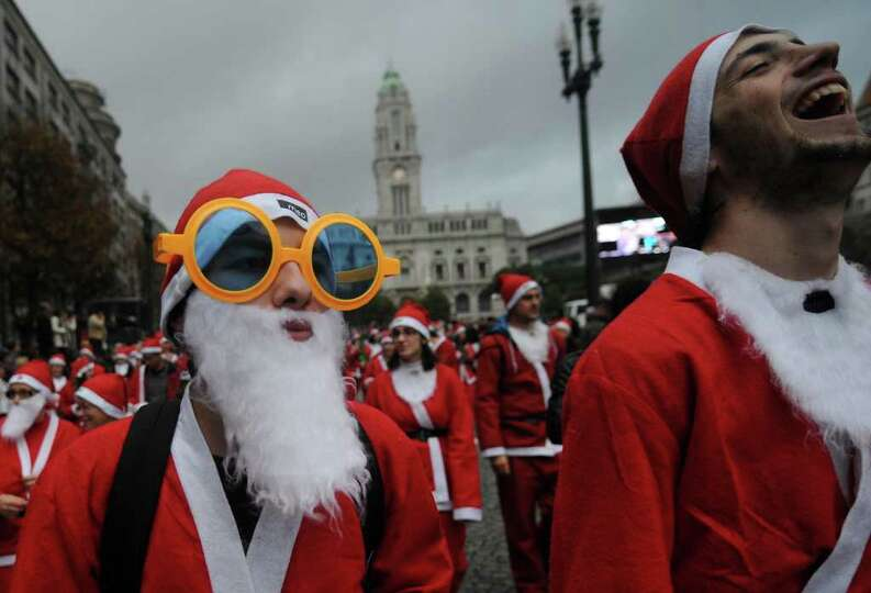 Revelers dressed as Santa Claus enjoy a laugh as they participate in the annual Santa Claus parade,