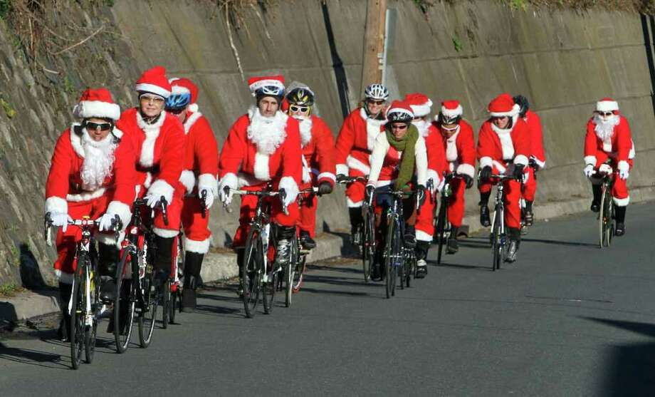 Members of the Empire Triathlon Club from Manhattan spread holiday cheer as they ride en masse, dressed at Santa Clauses, on South Piermont Avenue in Piermont, N.Y., Sunday  Dec. 11, 2011. The Santas were on their way back to the city after riding up to Nyack. Photo: Seth Harrison, Associated Press / The Journal News