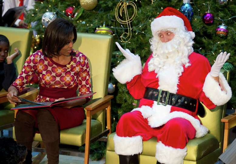 Santa Claus gestures toward first lady Michelle Obama as she reads
