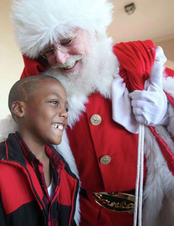 """Cancer patient Jayshawn Dixon, 8, greets Santa Claus during the """"Stuff the Sleigh"""" holiday party at the Firethorne Visitor Center Sunday, Dec. 11, 2011, in Katy. Approximately 19 children with cancer, 51 siblings and parents from the Texas Children's Hospital West Campus receive Christmas gifts. Photo: Mayra Beltran, Houston Chronicle / © 2011 Houston Chronicle"""