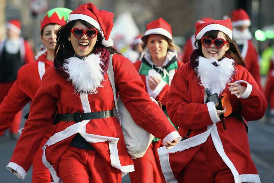 Participants dressed as Santa Claus smile as they take part in the Great Edinburgh Santa Run on December 11, 2011 in Edinburgh, Scotland. Around a thousand people took part in the annual fundraising event, with all money raised being donated to the charity 'When You Wish Upon a Star'. Photo: Jeff J Mitchell, Getty / 2011 Getty Images