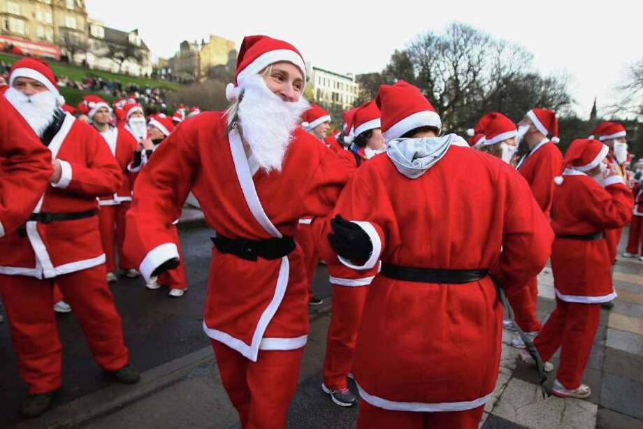 Participants dressed as Santa Claus dance as they prepare to take part in the Great Edinburgh Santa Run on December 11, 2011 in Edinburgh, Scotland. Around a thousand people took part in the annual fundraising event, with all money raised being donated to the charity 'When You Wish Upon a Star'. Photo: Jeff J Mitchell, Getty / 2011 Getty Images