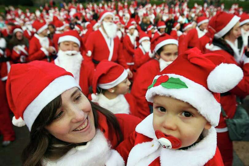 A woman holds a child dressed as Santa Claus as other participants prepare to take part in the Great