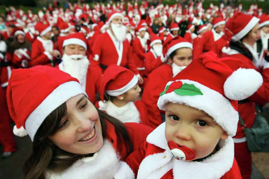 A woman holds a child dressed as Santa Claus as other participants prepare to take part in the Great Edinburgh Santa Run on December 11, 2011 in Edinburgh, Scotland. Photo: Jeff J Mitchell, Getty / 2011 Getty Images