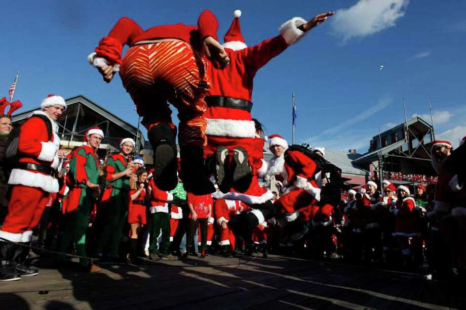 Revelers dressed as Santa Claus play jump rope during the annual SantaCon event December 10, 2011 in New York City. SantaCon is a mass gathering of revelers dressed as Santa Claus who take to the streets in cities across the country before Christmas. Photo: Allison Joyce, Getty / 2011 Getty Images