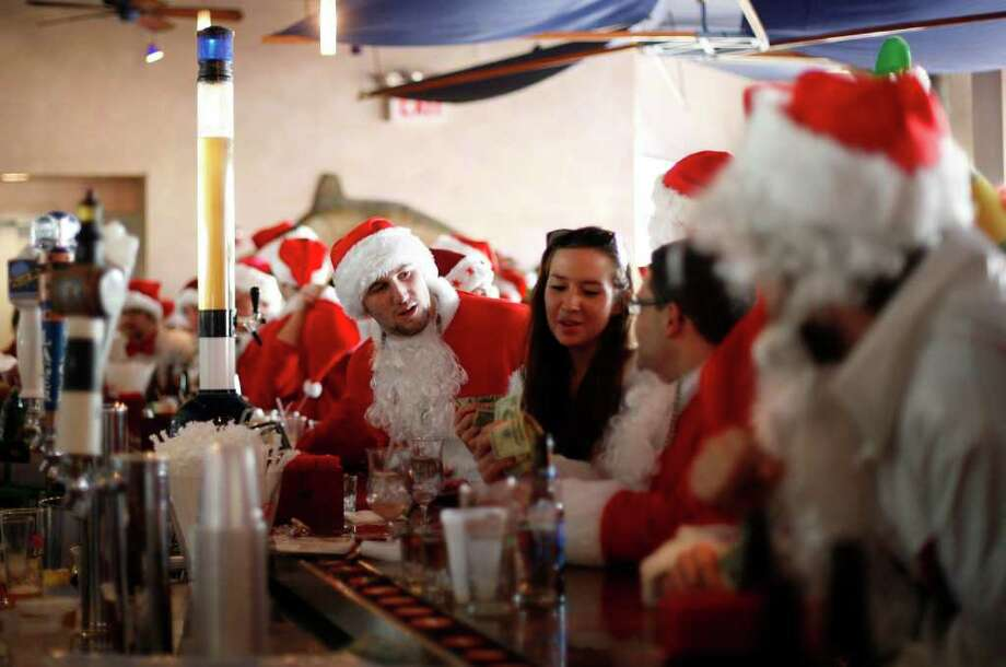 Revelers dressed as Santa Claus drink at a bar during the annual SantaCon event December 10, 2011 in New York City. SantaCon is a mass gathering of revelers dressed as Santa Claus who take to the streets in cities across the country before Christmas. Photo: Allison Joyce, Getty / 2011 Getty Images