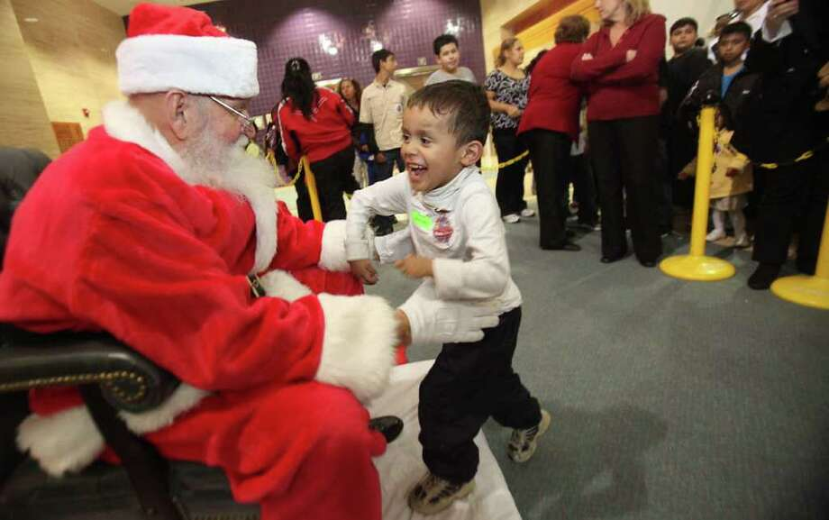 Santa greets with open arms patient Braulio Puente, 5, as he runs to Santa during the Shriners Hospital Tree Lighting Ceremony and Santa visit on Thursday, Dec. 1, 2011, in Houston.  Shriners Hospital is the first Holiday Lighting Ceremony of the season in the Texas Medical Center. Photo: Mayra Beltran, Houston Chronicle / © 2011 Houston Chronicle