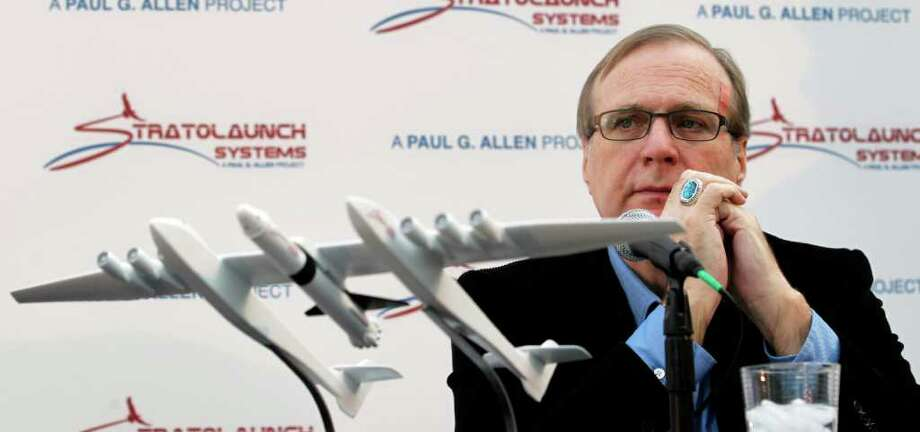 FILE-- Microsoft co-founder Paul Allen displays a model of Stratolaunch, which would use six 747 engines. Stratolaunch provided the first details about a new family of launch vehicles it has in the works, including two types of rockets and a reusable space plane that could someday carry astronauts to orbit. Photo: Elaine Thompson / AP