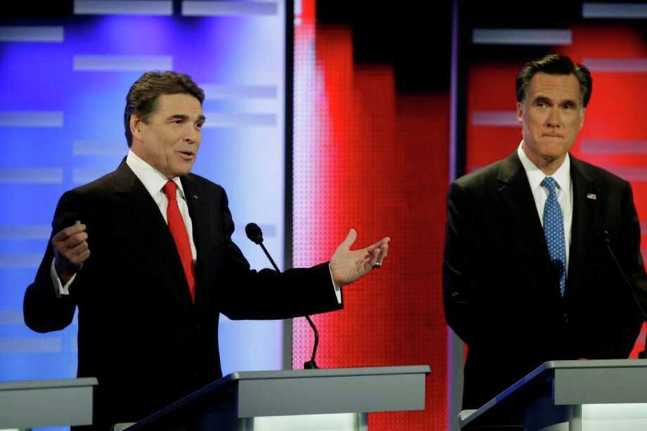 Republican presidential candidates Texas Gov. Rick Perry, left, and former Massachusetts Gov. Mitt Romney, right, take part in the Republican debate, Saturday, Dec. 10, 2011, in Des Moines, Iowa. Photo: AP