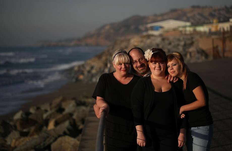 """Craig Miller with his wife Dawn Miller and their two children, Savanah, 17, and Skyler, 18, (rt) stand on the water's edge near their apartment on Tuesday. Dec. 6, in Pacifica, Calif. SOS helped Miller and his family with rent after after job loss set them back. """"If we didn't have the help we would have been evicted,"""" said Craig Miller. Photo: Mike Kepka, The Chronicle"""