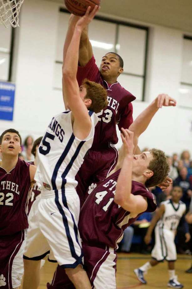 Bethel's Daniel Garvin (23) blocks a shot by Immaculate's Greg Minchik during the championship game of The New-Times Tip-Off Classic Saturday night at the Danbury War Memorial. Photo: Barry Horn