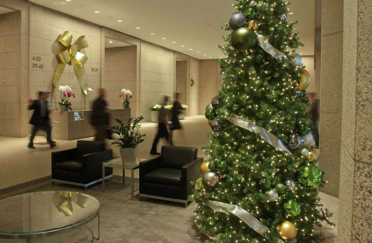 (For the Chronicle/Gary Fountain, December 5, 2011) A large golden bow above the security desk and decorated trees in the second floor lobby at Williams Tower. Property manager and building owner Hines has watched its capital spending on decor to keep expenses down, and often refreshes their decorations.
