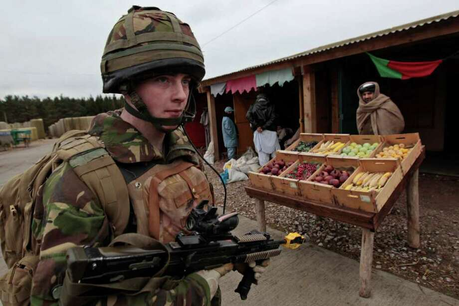A British soldier, from 1 Rifles, patrols through the market area of the 'Ishmara' village, a mock-up Afghan village that is been used by troops for training prior to deployment, at British forces' Stanford Training Area in eastern England, Friday, Jan. 14, 2011. Photo: Lefteris Pitarakis, Associated Press / AP