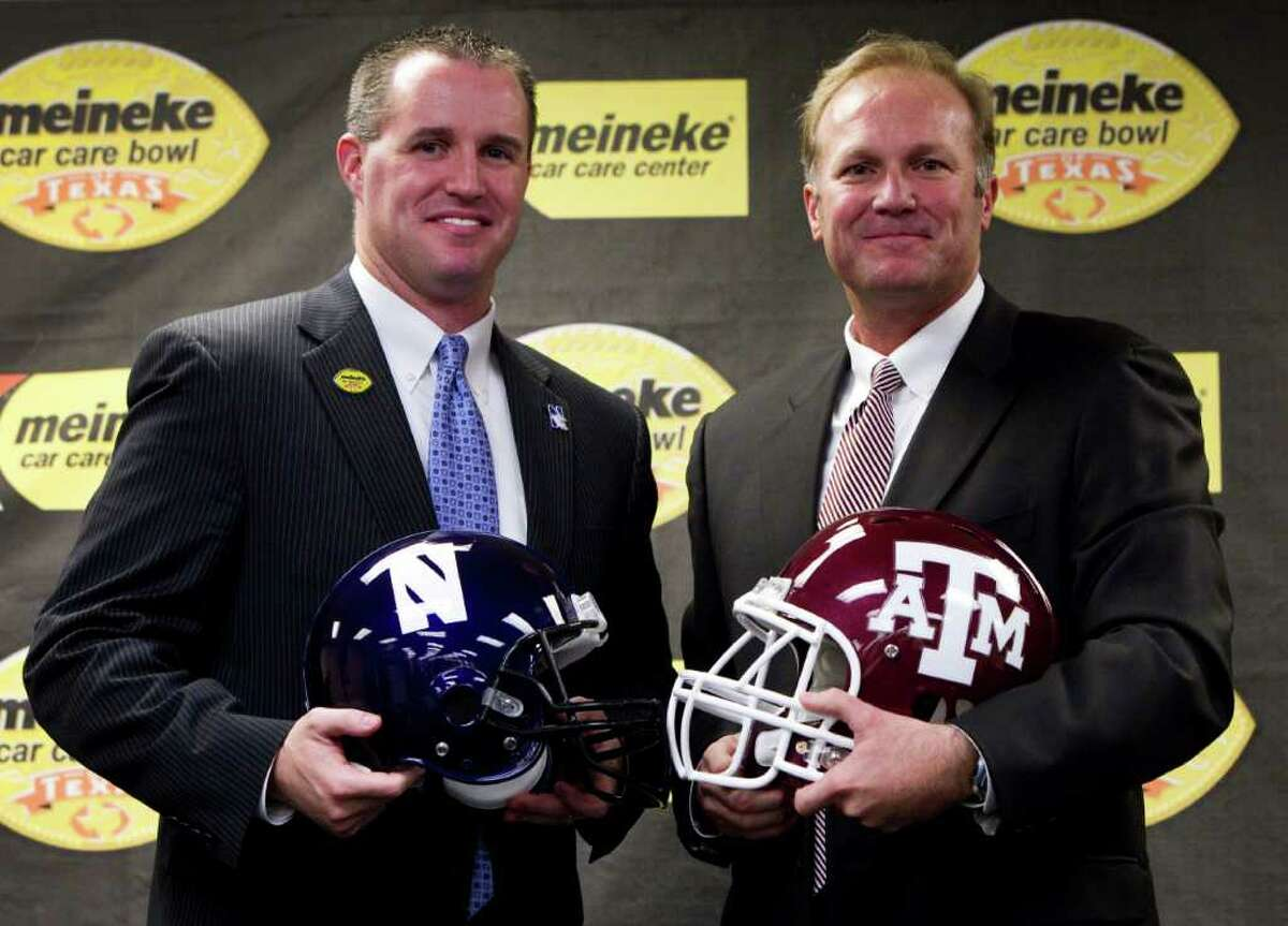 Northwestern head coach Pat Fitzgerald, left, and Texas A&M interim head coach Tim DeRuyter pose for photos following a news conference introducing the teams playing in the Meineke Car Care Bowl of Texas at Reliant Stadium. Thursday, Dec. 8, 2011, in Houston. Texas A&M will face Northwestern on December 31