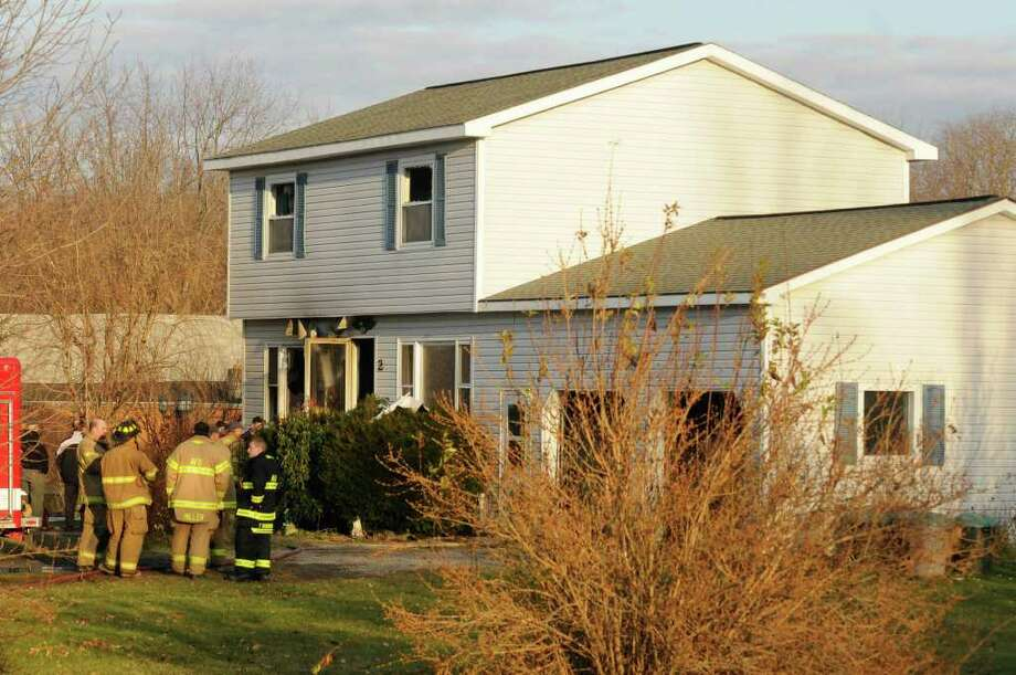 Fire investigators examine the scene of a fatal fire at 2 Marian Court in Altamont, NY Tuesday, Dec.13, 2011.( Michael P. Farrell/Times Union) Photo: Michael P. Farrell