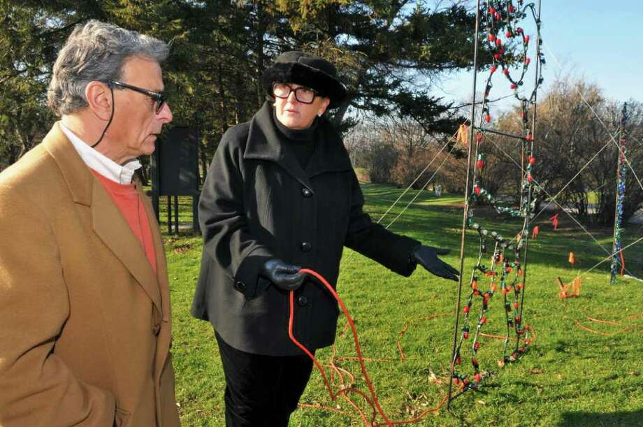 Members of the Washington Park Conservancy, Herb Starr, left, and Fran Ingraham, look over power cords on the ground at one of the displays at the holiday light show at Washington Park in Albany Tueday Dec. 13, 2011.  (John Carl D'Annibale / Times Union) Photo: John Carl D'Annibale / 00015766A