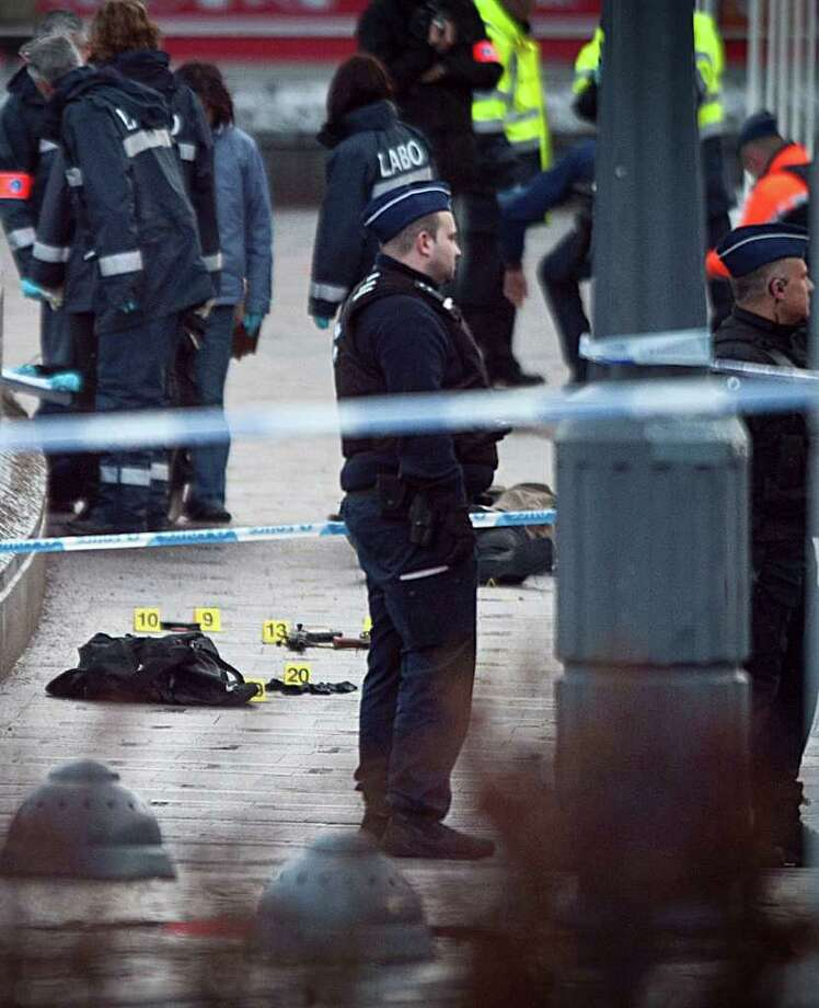 ADDS DETAIL OF BODY IN STREET - ALTERNATIVE VERSION OF MBER105 - Police stand next to evidence markers after an incident in Liege, Belgium, on Tuesday, Dec. 13, 2011 next to a body at centre right. Officials say an armed man who attacked people in a crowded square in the Belgian city of Liege on Tuesday had served time in jail for offenses involving guns, drugs and sexual abuse.They say he was on his way for police questioning when he launched the attack. Some people were killed and more than 70  people were wounded. La Libre Belgique newspaper reported that a 2-year-old girl was clinging to life. (AP Photo/dapd/ Timur Emek) Photo: Timur Emek / dapd