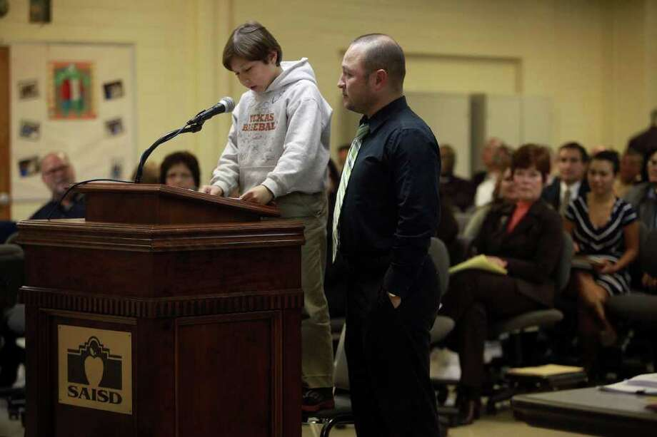 Art Gonzalez stands by as his son, 9-year-old soccer goalie Bishop Gonzalez, speaks about playing soccer in Alamo Stadium. Photo: LISA KRANTZ, Lkrantz@express-news.net / SAN ANTONIO EXPRESS-NEWS