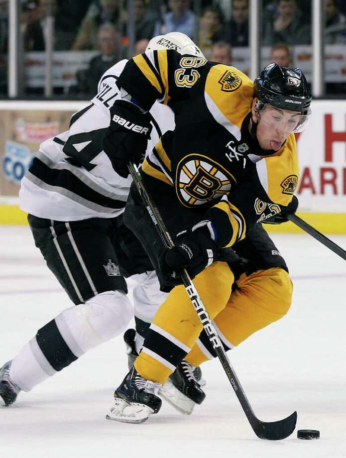 Boston Bruins left wing Brad Marchand (63) beats Los Angeles Kings right wing Justin Williams (14) to the puck in the second period of an NHL hockey game in Boston Tuesday, Dec. 13, 2011. (AP Photo/Elise Amendola) Photo: Elise Amendola
