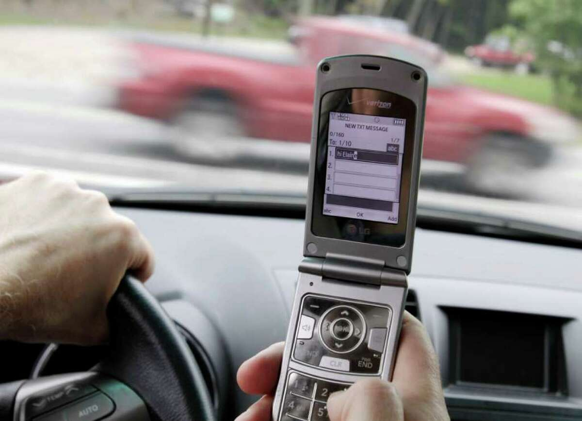 FILE - In this Sept. 20, 2011 file photo, a phone is held in a car in Brunswick, Maine. Texting, emailing or chatting on a cellphone while driving is simply too dangerous to be allowed, federal safety investigators declared Tuesday, Dec. 13, 2011, urging all states to impose total bans except for emergencies. (AP Photo/Pat Wellenbach, File)