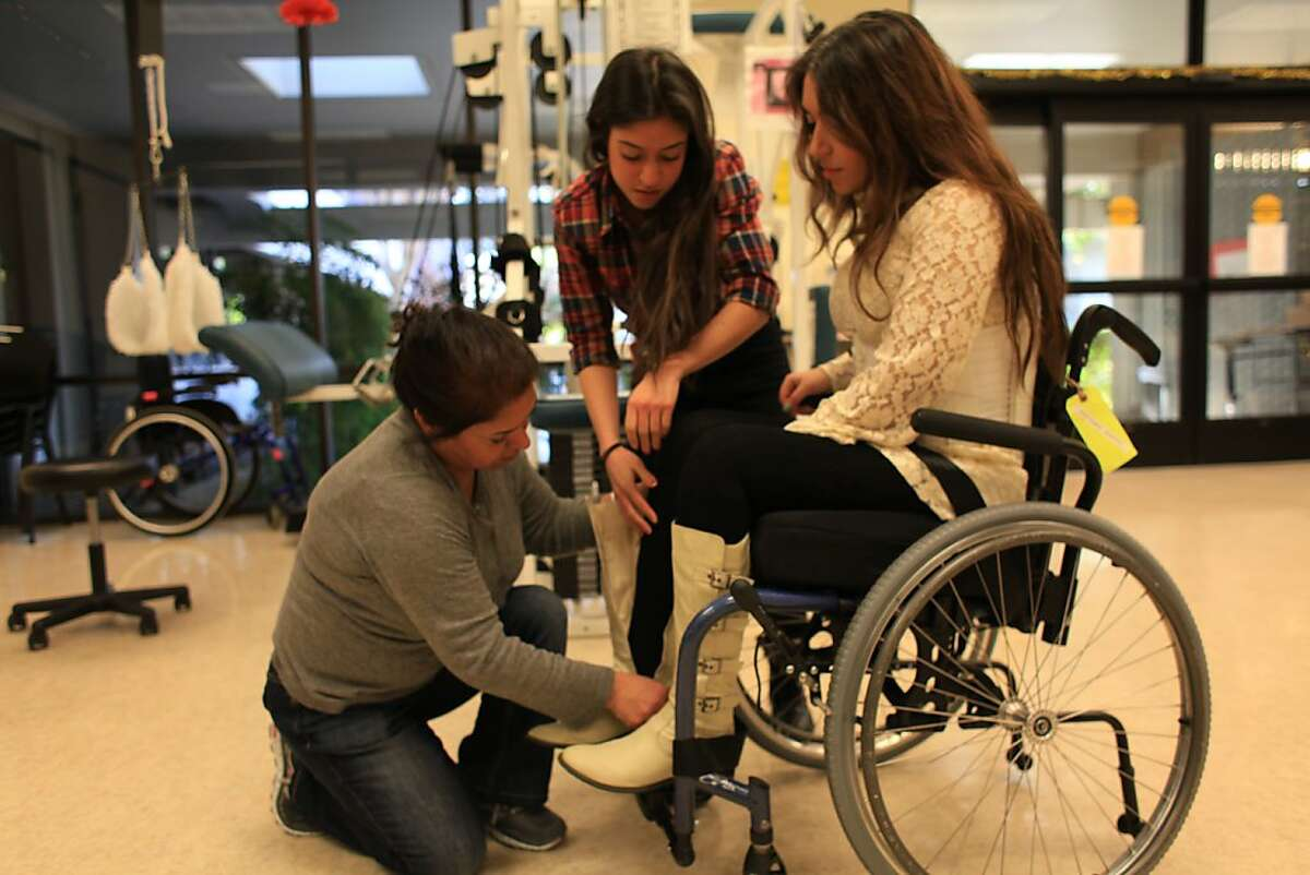 Katy Sharify (right), who received stem cell therapy before the study she was part of was cancelled, watches as her mother Zohreh Sharify (left) and sister, Julie Sharify (center) help put on her boots in the Cypress Semiconductor Spinal Cord Rehabilitation Gym at Santa Clara Valley Medical Center on Tuesday, December 13, 2011 in San Jose, Calif.
