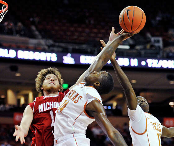 Texas guard J'Covan Brown, center, goes for the rebound against Nicholls State guard Chris Talkington, left, and Texas guard Myck Kabongo, right, during the first half of an NCAA college basketball game, Tuesday, Dec. 13, 2011, in Austin. Photo: Michael Thomas, Associated Press / FR65778 AP