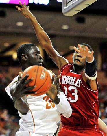 Texas forward Alexis Wangmene, left, looks to pass against Nicholls State guard Trevon Lewis, right, during the first half of an NCAA college basketball game, Tuesday, Dec. 13, 2011, in Austin. Photo: Michael Thomas, Associated Press / FR65778 AP