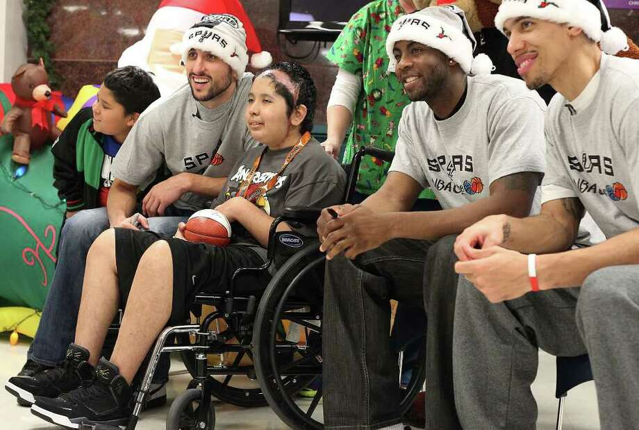Spurs players Manu Ginobili (second from left), James Anderson and Danny Green pose for a photo with 15-year-old Oscar Hernandez (third from left) and his younger brother Jared during a visit at Christus Santa Rosa Children's Hospital on Tuesday, Dec. 13, 2011. The visit by players marked the 15th year that patients from the hospital met with the team. About 50 patients and family members waited in line and received autographed miniature basketballs as souvenirs. Photo: Kin Man Hui, SAN ANTONIO EXPRESS-NEWS / San Antonio Express-News
