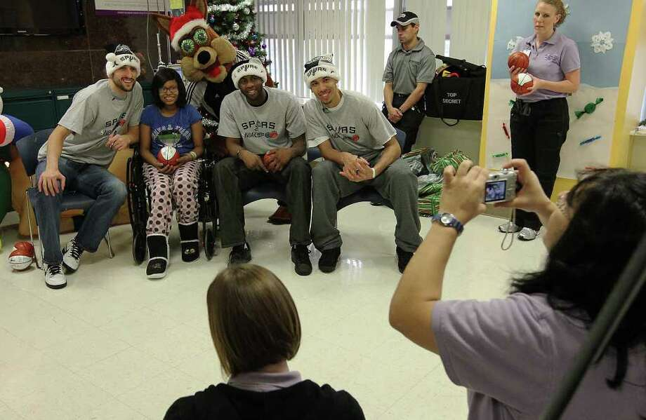 Spurs' Manu Ginobili (from left), patient Zamira Lawson, James Anderson and Danny Green pose for a picture during a visit at Christus Santa Rosa Children's Hospital on Tuesday, Dec. 13, 2011. The visit by players marked the 15th year that patients from the hospital met with the team. About 50 patients and family members waited in line and received autographed miniature basketballs as souvenirs. Photo: Kin Man Hui, SAN ANTONIO EXPRESS-NEWS / San Antonio Express-News
